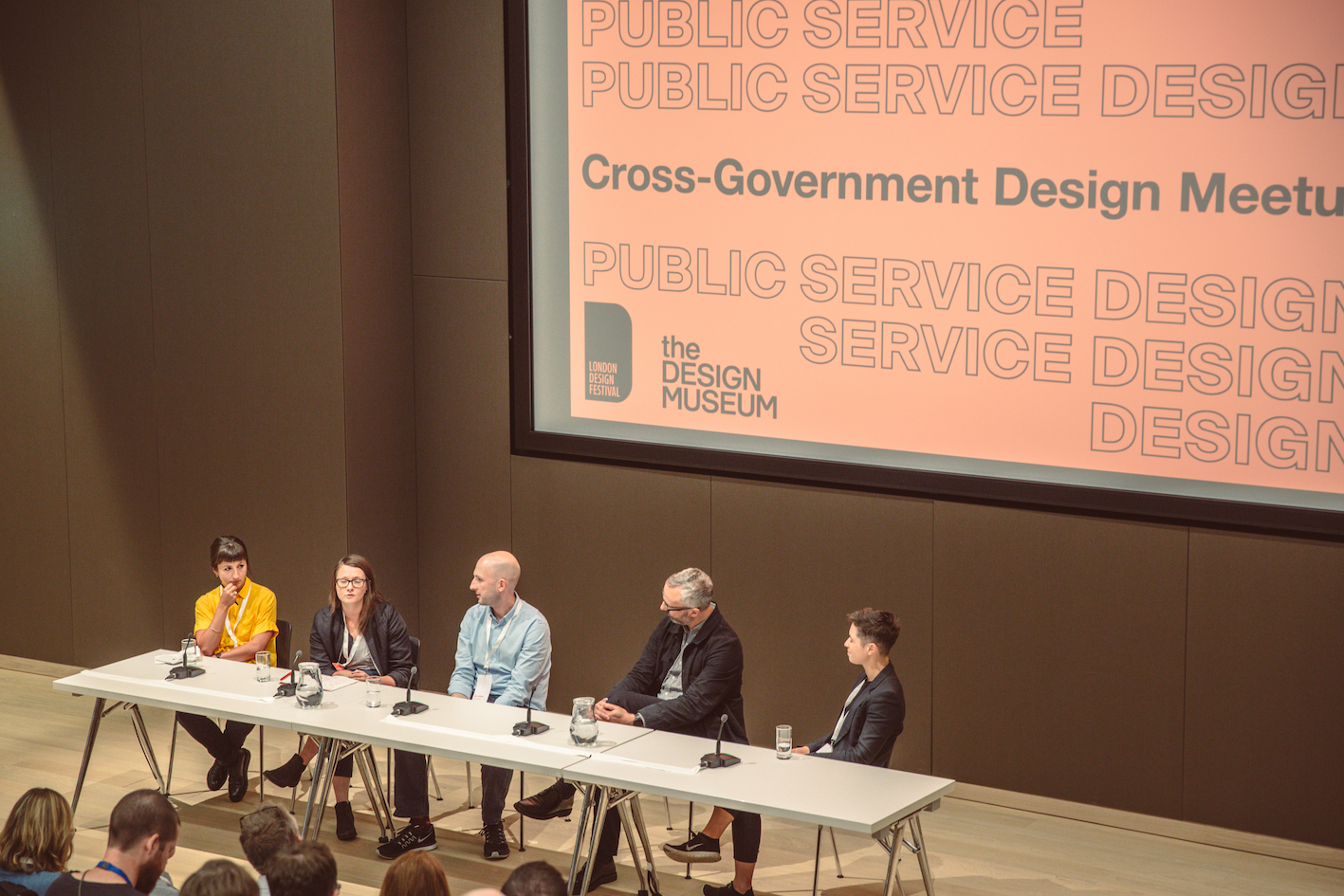 Five people sitting at a table in front of a screen saying 'Cross-Government Design Meetup'