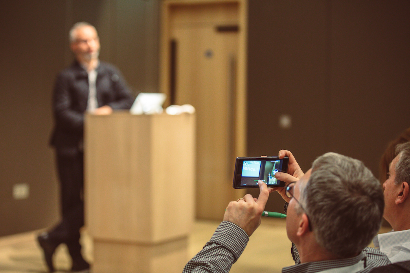 A man standing at a lectern and being photographed by another man