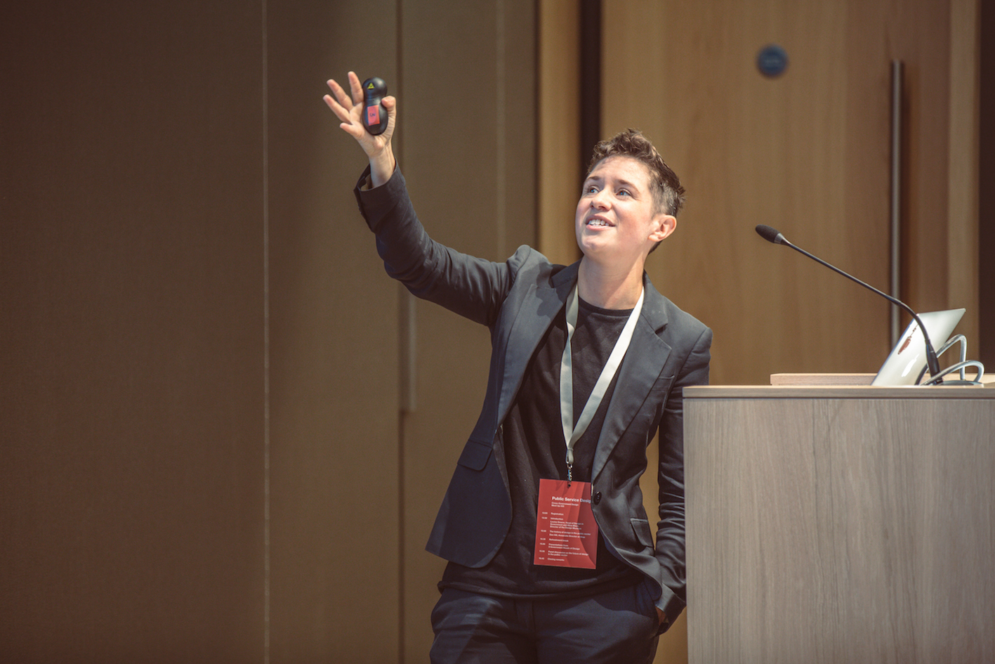 Lou standing at a lectern and gesturing at a screen