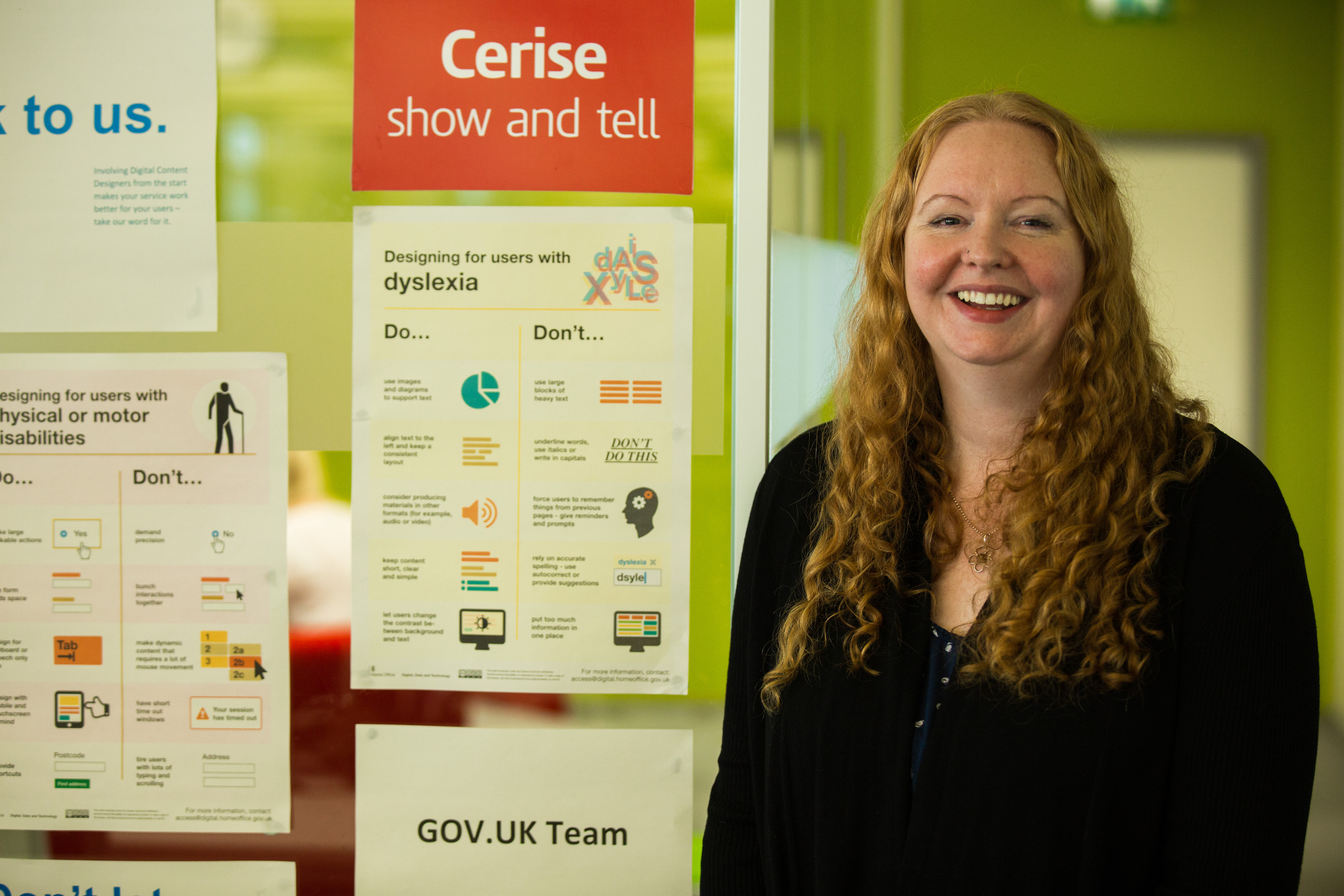 Jane standing next to a poster that has advice on designing for people with dyslexia