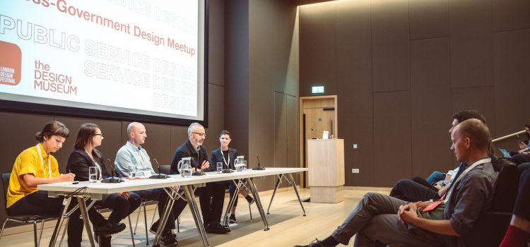 A panel of speakers in front of an audience
