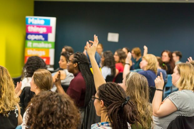 An image of people with their hands raised in the audience of a show and tell