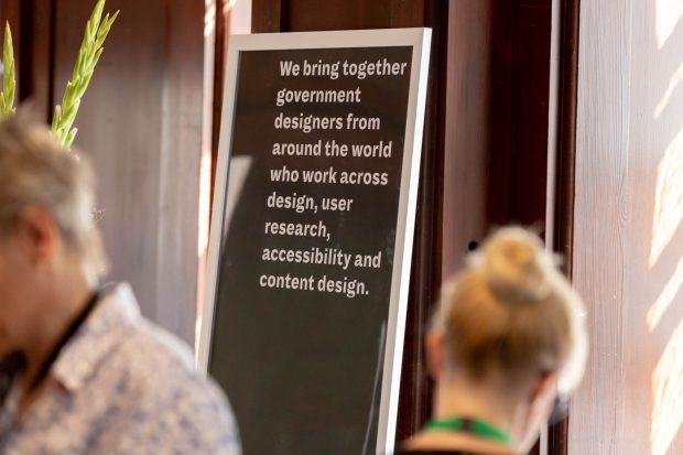 "A poster at last year's International Design in Government Conference, which says: ""We bring together government designers from around the world who work across design, user research, accessibility and content design."""