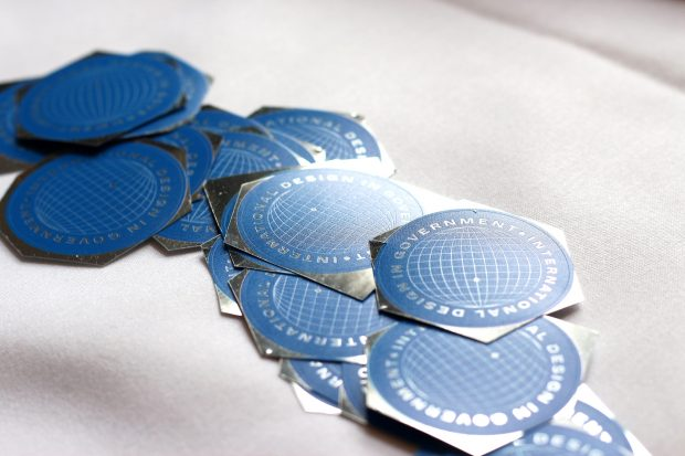 A dozen blue stickers with an illustration of the globe and the words 'International Design in Government' on a white table cloth