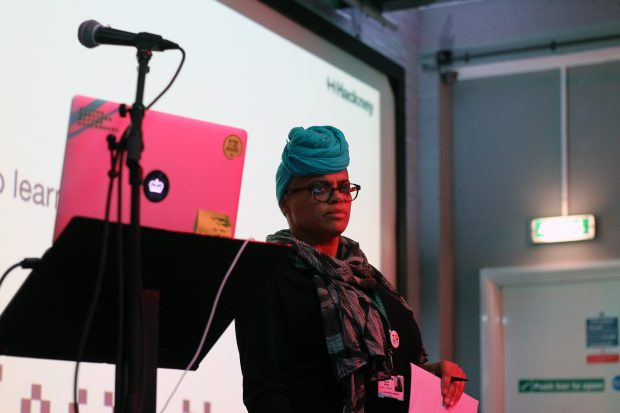 Joanne Moore, service design lead at Hackney Council, standing next to a computer and microphone while overseeing a workshop during a cross-government service design meetup, co-run with Hackney Council