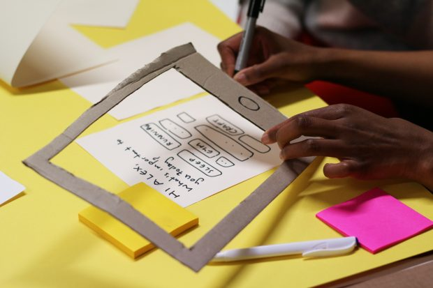 A woman with darker skin tone is preparing a mockup of a smartphone interface, the phone is a cardboard frame, the screen is small sheet of paper, the person is drawing the user interface with a pen, coloured sticky notes are surrounding her