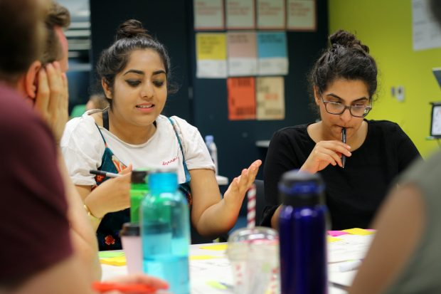 A group of participants in GDS design training working together at a table – two female participants with darker skin tones in focus