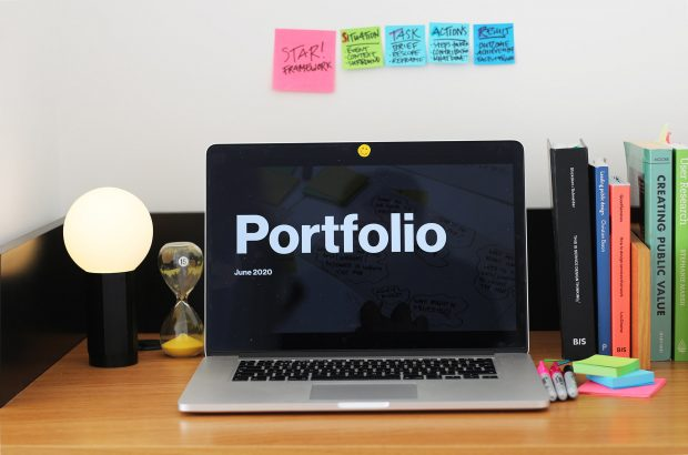 A laptop computer on a wooden desk, its screen shows the title page of a design portfolio