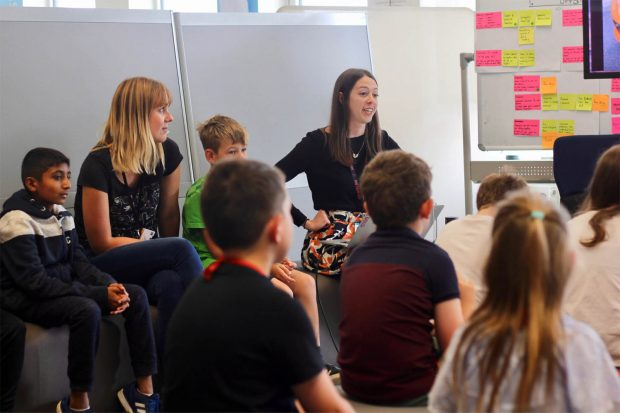 Carolina Pizatto, service designer at the Ministry of Justice, speaking in front of a group of kids of different ethnicities, surrounded by whiteboards with colourful stickie notes