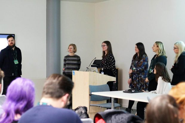 6 female designers from the Ministry of Justice presenting in front of their colleagues at a cross-government design meeting in London in February 2020