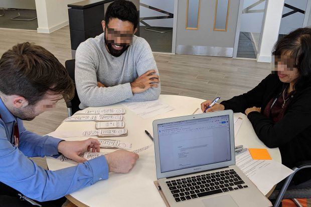 Three people of different ethnicities smiling, sitting around a table in a co-creation workshop looking at paper prototypes of mobile service interfaces