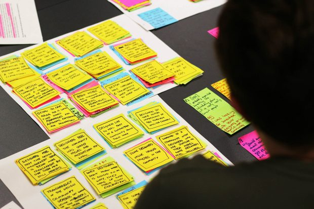 Small piles of sticky notes on a table, clustered and summarised with a person looking at them