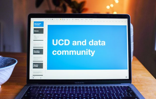 A computer standing in a room, its screen shows a slidedeck reading 'UCD and data community'