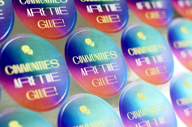 A sheet of colourful circular stickers all saying: Communities are the glue!