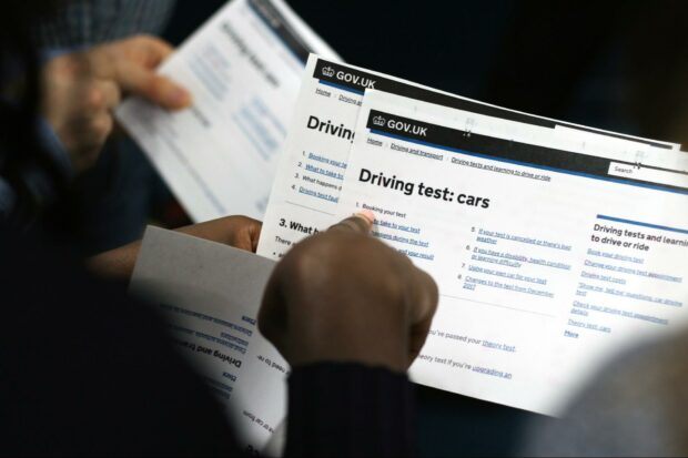 2 people standing next to each other holding print-outs of service pages from GOV.UK; in the foreground, a black woman pointing at 'booking your test', part of driving test service for cars